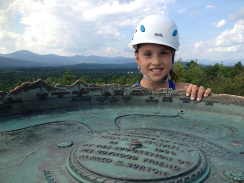 Jessica at the cool summit marker with Mount Washington far behind her
