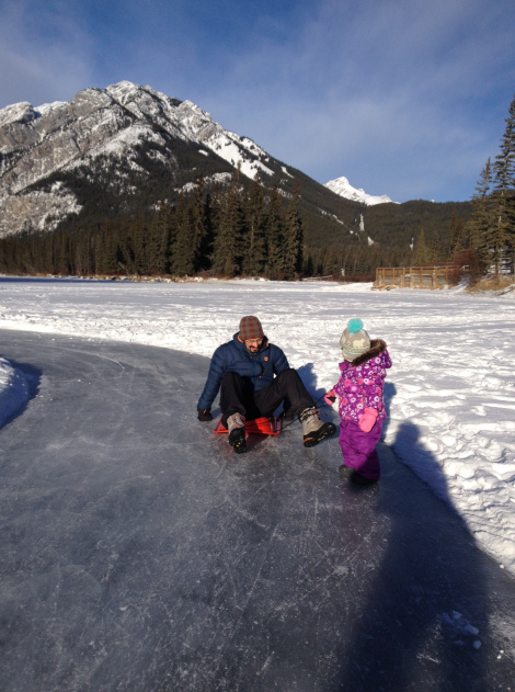 Somehow skating on the Bow River turned into pulling dad on the sled. Photo Meghan J. Ward.